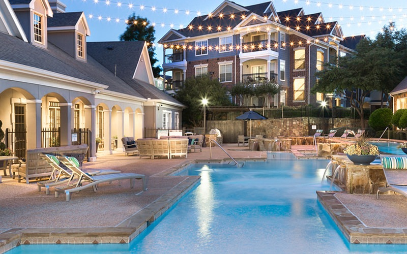 Large Resort-Style Pool Area With Sunbathing Chairs All Around It & String Lights.